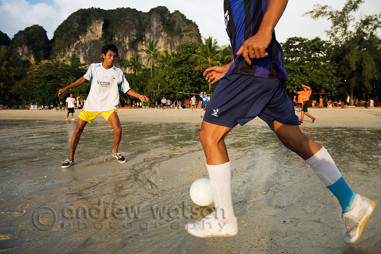 Locals play beach football on the sands of Hat Rai Leh West.  Railay, Krabi, THAILAND