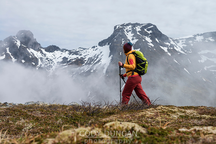 Female hiker hiking through cloudy weather towards summit of Volandstind mountain peak, Flakstadøy, Lofoten Islands, Norway