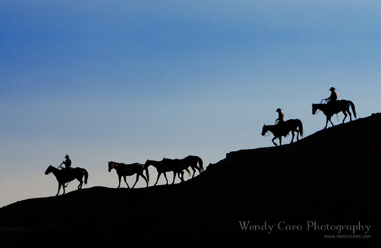 Silhouette of wranglers leading small group of horses down the mountain, back to the herd, Big Horn Mountains, Wyoming.
