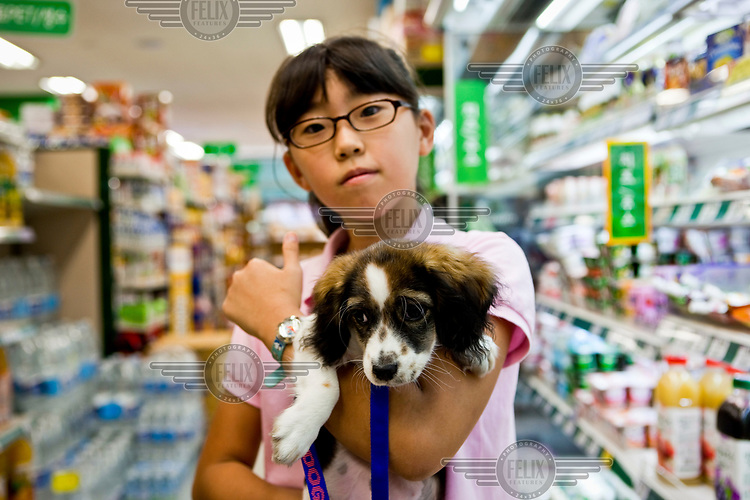 A girl shopping with her puppy in a supermarket.