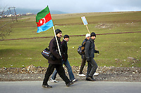 Azerbaijan. Ismaelly region. Gabaca. Four men walk on the concrete road and will reach the capital Baku on foot to pay their tribute to the grave of Heidar Aliev. A man carries on his shoulder a picture of the deceased political leader Heydar Aliyev ( May 10, 1923 - December 12, 2003), also spelled as Heidar Aliev, Geidar Aliev, Haydar Aliyev. He was the president of Azerbaijan for the New Azerbaijan Party from June 1993 to October 2003. Another man carries the flag of Azerbaijan. The flag is a national symbol and consists of three equal horizontal bands, blue, red, and green; a white crescent and an eight-pointed star (Rub El Hizb) are centered in the red band. The eight points of the star stand for the eight branches of the Turkic people. The blue band is the color of the Turks, the green is for Islam and red is for progress. The official colours and size were adopted on February 5, 1991. © 2007 Didier Ruef