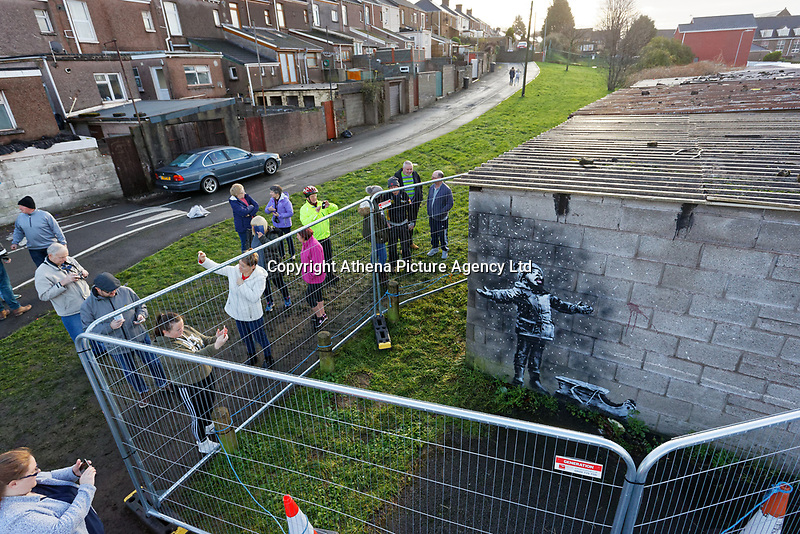 "Pictured: People arrive to see and take pictures of the Banksy graffiti on a garage in Port Talbot, Wales, UK. Thursday 20 December 2018<br /> Re: The artist Banksy has confirmed that a new graffiti piece that has appeared in Port Talbot, south Wales is his.<br /> He announced on Instagram: ""Season's greetings"" - with a video of the artwork in the Taibach area of Port Talbot.<br /> The image appears on two sides of a garage in a lane near Caradog Street, depicting a child enjoying snow falling - the other side reveals it is a fire emitting ash.<br /> The owner of the garage said he had not slept over fears it might be vandalised."