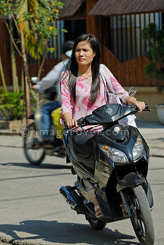 Asia, Vietnam, Hue. Vietnamese woman riding a motorbike through Hue.