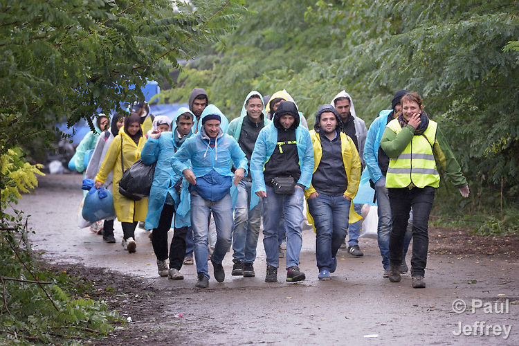 Escorted by a Czech volunteer (in the yellow vest), refugees approach the border into Croatia near the Serbian village of Berkasovo. Hundreds of thousands of refugees and migrants from Syria, Iraq and other countries have flowed through Serbia in 2015, on their way to western Europe.