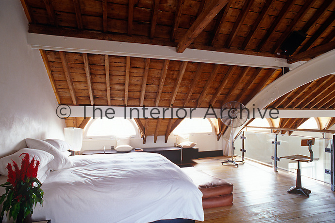The wooden rafters, framed with white steel struts, have been made a feature of this gallery bedroom