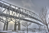 The sun attempts to break through the clouds, mist and snow at the Blue Water Bridges. The bridges span the St. Clair River joining Point Edward, Ontario to Port Huron, Michigan.