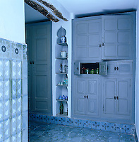 Hand-painted tiles cover the floor and walls of this kitchen which also has a variety of blue-painted built-in cupboards