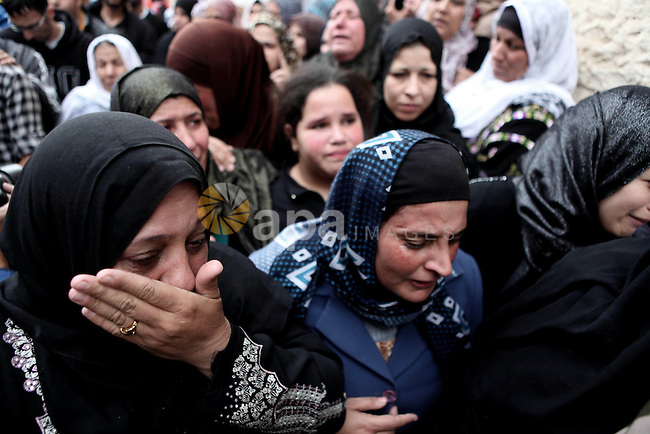 Relatives mourn during the funeral of 21-year old Palestinian Imad Jawabreh during his funeral in the West Bank town of Hebron, who died after being hit in the chest by bullets near Al-Aroub refugee camp, close to route 60, the main north-south road in the Palestinian enclave during clashes with the Israeli army on November 11, 2014. The Israeli army confirmed troops had opened fire at demonstrators who were stoning cars in the area. Photo by Mamoun Wazwaz