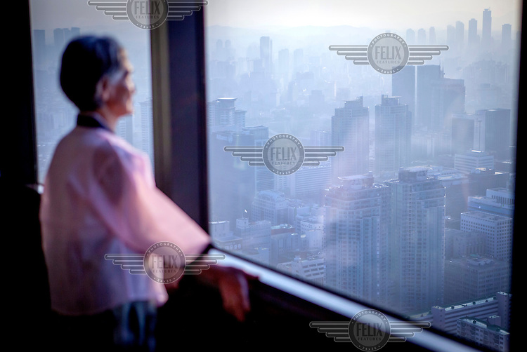 "A woman in traditional Korean clothes watches the Seoul skyline at ""The 63 Building"", officially the 63 City, a skyscraper on Yeouido Island."
