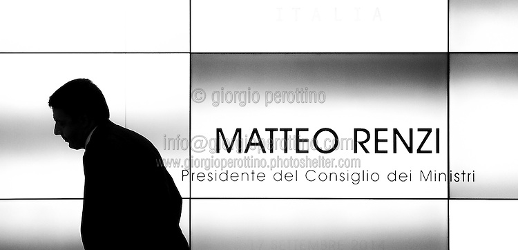 Italian Prime Minister Matteo Renzi walks close to a video wall during a meeting  in Turin, September 17, 2014.