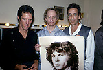 in 1984 the remaining members of  The Doors, John Densmore, Robby Krieger and Ray Manzarek hold up a photo of Jim Morrison at a party celebrating the release of the music video for L.A. Woman that was directed by Ray Manzarek.