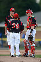 Batavia Muckdogs pitcher coach Brendan Sagara (28) talks with pitcher Brian Ellington and catcher Chad Wallach during a game against the Aberdeen Ironbirds on August 9, 2013 at Dwyer Stadium in Batavia, New York.  Aberdeen defeated Batavia 8-5  (Mike Janes/Four Seam Images)