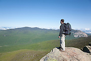 A hiker enjoys the views from the summit of Mount Liberty during the summer months in the White Mountains, New Hampshire USA. Cannon Cliff can be seen in the background.