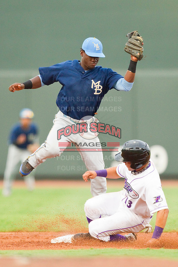 Odubel Herrera #24 of the Myrtle Beach Pelicans comes down with a high throw as Carlos Sanchez #13 steals second base at BB&T Ballpark on July 5, 2012 in Winston-Salem, North Carolina.  The Dash defeated the Pelicans 12-5.  (Brian Westerholt/Four Seam Images)