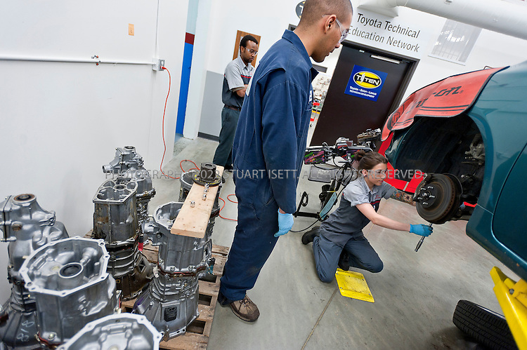 11/4/2010--Shoreline, WA, USA..Kaylin MacCoy, 22 (right) works on a  Toyota's brake system at the Shoreline Community College just north of Seattle, WASH. Left & behind: Stephen Kea, 28. Left front: Peter Menage, 20..The students are enrolled on a Skills for America jobs training program at the Shoreline Community College  that trains and places students for automotive technician jobs at car dealerships, working with local Honda and Toyota dealerships among others...©2010 Stuart Isett. All rights reserved