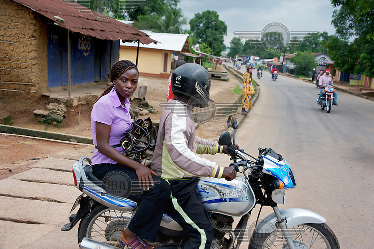 Baindu Koroma, a paralegal who works for Timap for Justice, riding a motorbike taxi on her way to Bo central police station. <br /> Her work includes making regular visits to police stations, the prison, and the courts to monitor whether people are being afforded their lawful rights, for example, the right to bail, legal representation, detention without charge, etc, and if not to advocate on their behalf.