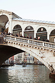 ITALY, Venice. Tourists lined up along the Rialto Bridge and looking at a view of the Grand Canal.