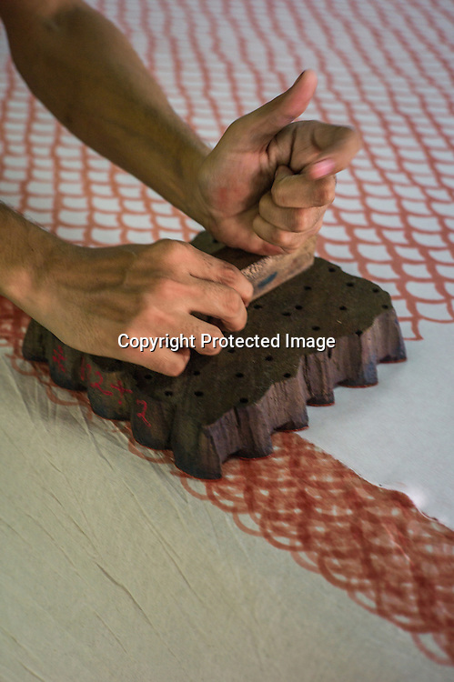Local Rajasthani printer prints designs on fabric using wooden blocks at a factory in Jaipur, Rajasthan, India.  Photo: Sanjit Das/Panos for Le Point