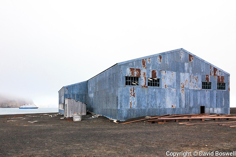 "A ruined British hanger is one of the remaining buildings at the abandoned Norwegian whaling base and British military and reasearch base at Whalers bay, on Deception island in the South Shetland Islands near the Antarctic Peninsula.  The Quark Expeditions shi p, the ""Sea Spirit,"" is anchored in the bay."