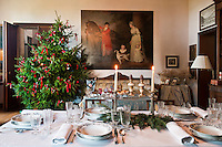 An antique painting on the wall with a Christmas tree elegantly decorated with red bows and a table laid fpr Christmas dinner with delicate crockery