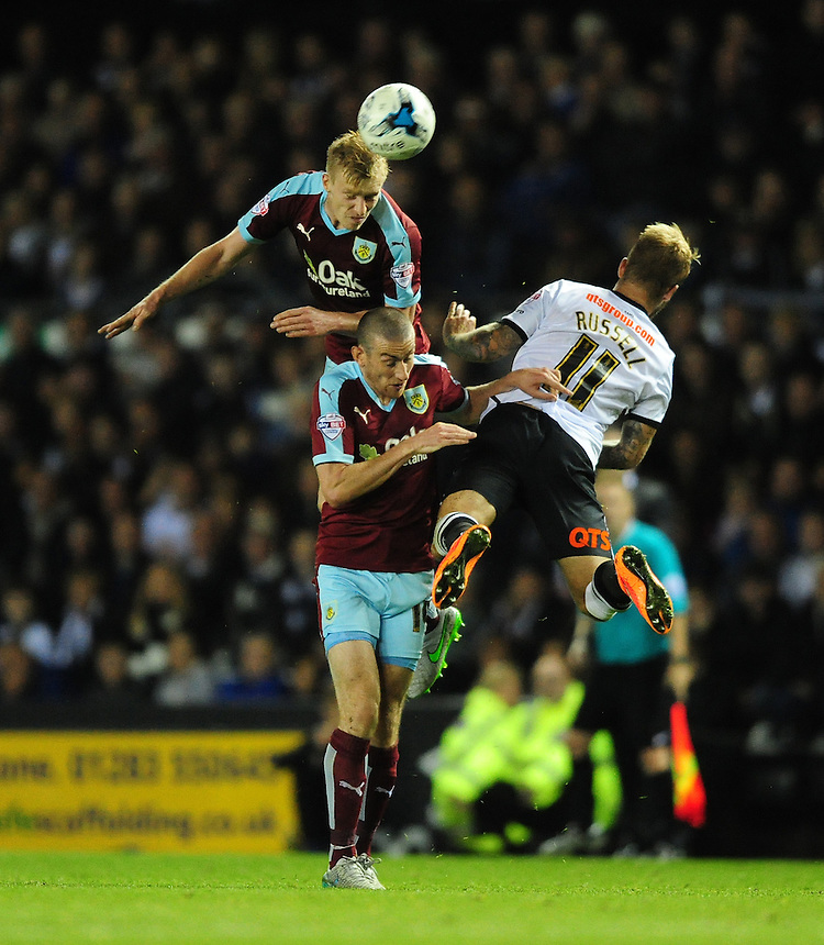 Burnley's Ben Mee out-jumps team-mate Burnley's David Jones and Derby County's Johnny Russell to win a high ball<br /> <br /> Photographer Chris Vaughan/CameraSport<br /> <br /> Football - The Football League Sky Bet Championship - Derby County v Burnley - Monday 21st September 2015 - iPro Stadium - Derby<br /> <br /> &copy; CameraSport - 43 Linden Ave. Countesthorpe. Leicester. England. LE8 5PG - Tel: +44 (0) 116 277 4147 - admin@camerasport.com - www.camerasport.com
