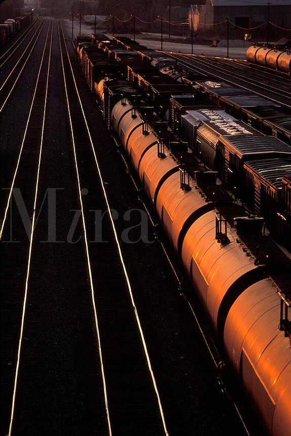 rail cars on tracks at sunset