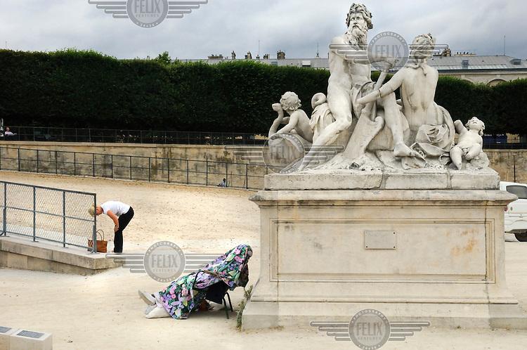 Someone sleeps under a blanket in the Tuileries gardens (Jardin des Tuileries).