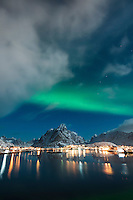 Northern lights shine in sky over Reine, Moskenesøy, Lofoten Islands, Norway