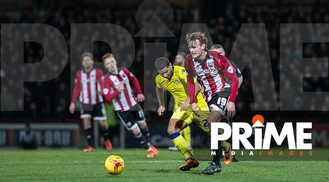 John Swift of Brentford heads away from Liam Bridcutt of Leeds United during the Sky Bet Championship match between Brentford and Leeds United at Griffin Park, London, England on 26 January 2016. Photo by Andy Rowland / PRiME Media Images.