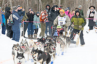 Lev Shvarts and team run past spectators on the bike/ski trail near University Lake with an Iditarider in the basket and a handler during the Anchorage, Alaska ceremonial start on Saturday, March 7 during the 2020 Iditarod race. Photo © 2020 by Ed Bennett/Bennett Images LLC