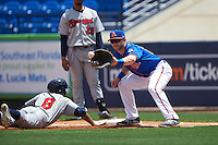 St. Lucie Mets first baseman Kevin Taylor (12) waits for a throw as Johnny Davis (8) dives back to the bag during a game against the Brevard County Manatees on April 17, 2016 at Tradition Field in Port St. Lucie, Florida.  Brevard County defeated St. Lucie 13-0.  (Mike Janes/Four Seam Images)