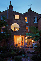 The rear view of a Victorian terraced house that has been modernised. An upper storey room has been fitted with a large porthole window, while sliding glass doors lead out onto a decked terrace.