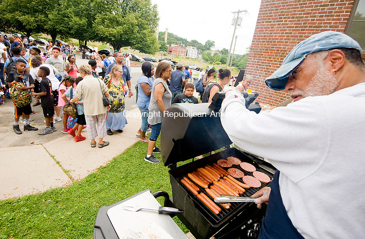 WATERBURY, CT-081217JS01-- Church trustee Rondell Bulls, right, tends to the grill as guests line up for food during the second annual Grace Baptist Church Community Day and Back-to-School give away Saturday at the Grace Baptist Church in Waterbury. Children were givenback packs filled with school items along with a picnic and games. <br /> Jim Shannon Republican-American