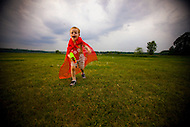A young boy with glasses wearing a red cape runs through a field with his bubble gun toy.