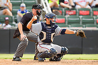 Rome Braves catcher Ryan Query #25 throws the ball back to his pitcher as home plate umpire Junior Valentine looks on during the South Atlantic League game against the Kannapolis Intimidators at CMC-Northeast Stadium on August 5, 2012 in Kannapolis, North Carolina.  The Intimidators defeated the Braves 9-1.  (Brian Westerholt/Four Seam Images)