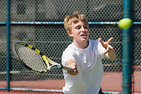 Teenage boy hitting tennis ball with forehand.  Ball in photo.