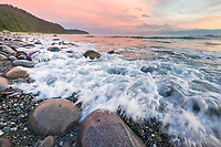 Waves at sunset along the rocky shore in the Gulf of Alaska, Pacific Ocean.