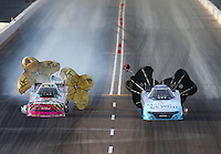 Feb 21, 2015; Chandler, AZ, USA; NHRA funny car driver Tommy Johnson Jr (right) races alongside Courtney Force during qualifying for the Carquest Nationals at Wild Horse Pass Motorsports Park. Mandatory Credit: Mark J. Rebilas-