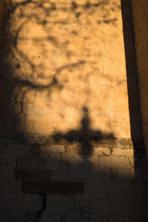 Shadow of a cross on the wall of the Monastery of Sant Cugat, Barcelona, Catalonia, Spain. Monestir de Sant Cugat, Catalunya, Espanya