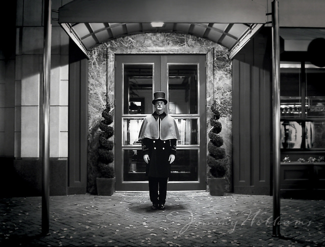 A doorman stands up straight outside of the entrance to an upscale hotel