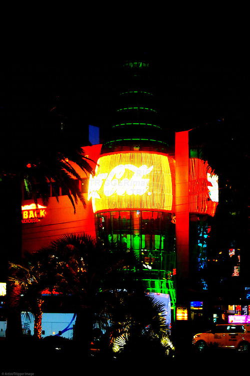 The illuminated Coca Cola Bottle of the Everything Coca Cola shop on Las Vegas Boulevard in the night .