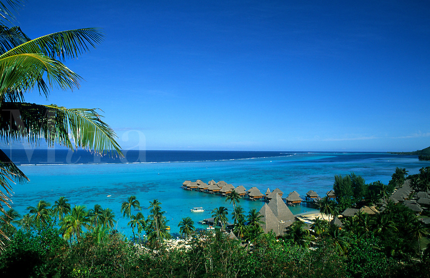 Huts extend into tropical water, Tahiti, Bora Bora, French Polynesia, South Pacific on holiday