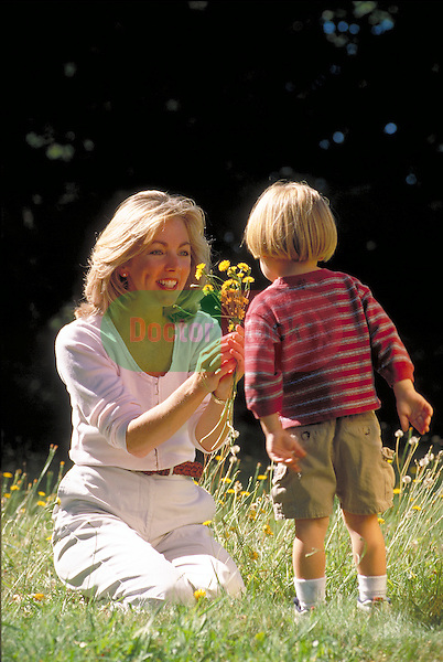 young boy giving mother flowers