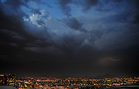 Lightning strike bolt thunderstorm monsoon storm thunderstorm Phoenix Arizona city sky lights urban chaser chasing building mountain