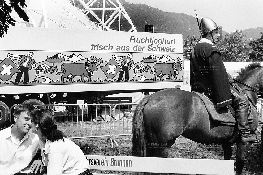 Switzerland. Canton Schwyz. Brunnen. A flirting couple, seated on a wood bench. A horseman, dressed as an antique warrior, is getting ready for the parade during the Swiss costum's fair. A truck is parked and the lorry's towing shows a large advertisement for fresh yoghurt with an alpine countryside landscape, a farm and cows in meadows, a peasant with traditional clothes throwing a swiss flag. © 1991 Didier Ruef