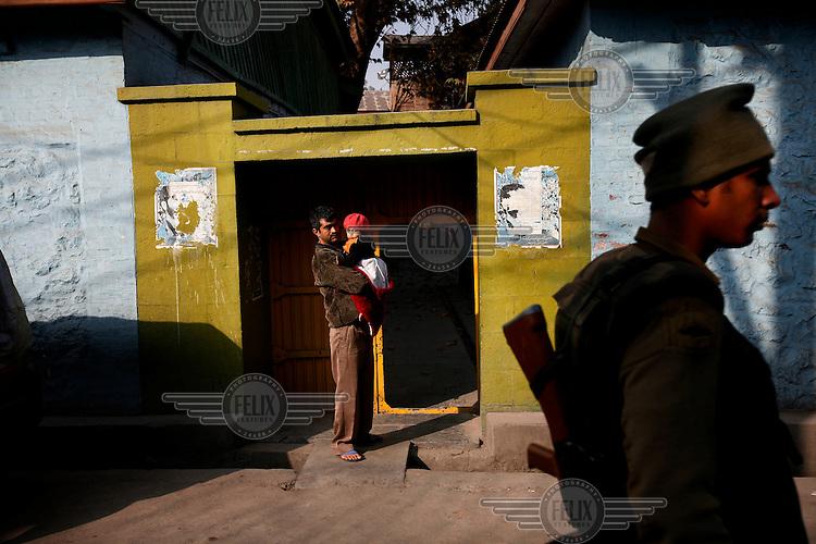 475.9.Årets reportasje utland.I KONFLIKTENS HJERTE /  THE HEART OF THE CONFLICT..En mann med sin datter på armen ser på når en patrulje fra det paramilitære politiet går inn for å håndheve et portforbud i sentrale Srinigar, indisk-kontrollert Kashmir. Portforbudet ble innført for å hindre politiske protester. Kashmir har vært kilden til to kriger mellom India og Pakistan, et voldelig opprør, og en rekke terroraksjoner...A man with daughter watches as a patrol of CRPF paramilitary police enforce a curfew imposed to stop separists gather for a political demonstration in Srinagar, Kashmir, India. Kashmir has been at the center of conflict since for a long time, sparking two wars between India and Pakistan, a militant uprising and a number of terrorist attacks...DIGITALT.06112008.SRINAGAR,INDIA