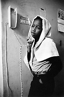 "USA. New York City. Spanish Harlem. Willie is talking on the telephone while his head and hair are covered by a white towel. The Puerto Rican family lives below the poverty line and receives public assistance (AFDC, Home Relief, Supplemental Security Income and Medicaid). The family resides in units managed by the New York City Housing Authority (NYCHA) which provides housing for low income residents. NYCHA administers rental apartments in facilities, popularly known as ""projects"". Spanish Harlem, also known as El Barrio and East Harlem, is a low income neighborhood in Harlem area. Spanish Harlem is one of the largest predominantly Latino communities in New York City. 15.06.86 © 1986 Didier Ruef . ..."