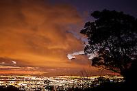 Orange sunset over Honolulu city lights