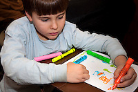 Boy age 7 drawing with Magic Marker highlighter pens. St Paul Minnesota USA