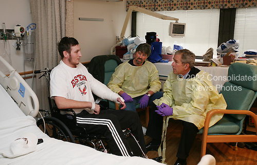 Bethesda, MD - December 19, 2007 -- United States President George W. Bush sits and visits with United States Marine Lance Corporal Michael Stilson of Clarkson, West Virginia, and his father, Robert Stilson, at the National Naval Medical Center in Bethesda, Maryland, Wednesday, December 19, 2007. Stilson is recovering from injuries sustained in Operation Iraqi Freedom..Credit: Joyce N Boghosian - White House via CNP